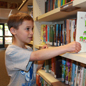 Elementary student pulls a book off the library shelf